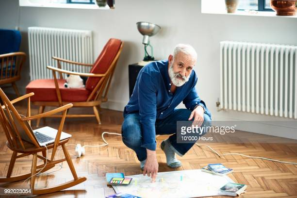 portrait of senior man crouching on floor with map - one senior man only stock pictures, royalty-free photos & images