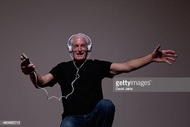 Portrait of senior man dancing to MP3 player on headphones