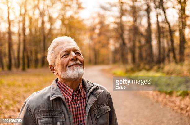 portrait of senior man enjoying an autumn day in the forest. - non urban scene stock pictures, royalty-free photos & images