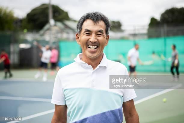portrait of senior man enjoying tennis - スポーツ  ストックフォトと画像