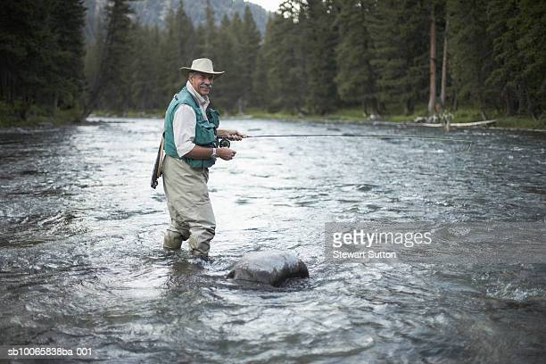 portrait of senior man flyfishing in river - wading stock pictures, royalty-free photos & images