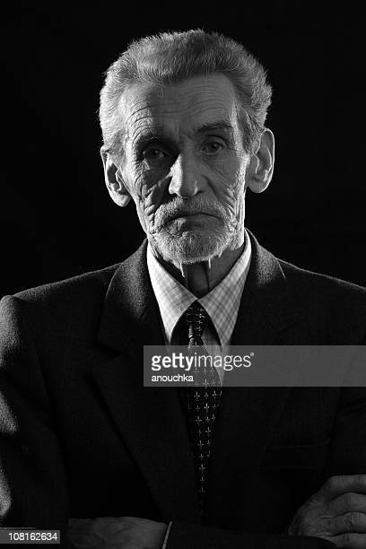 portrait of senior man folding arms, black and white - rich old man stock photos and pictures
