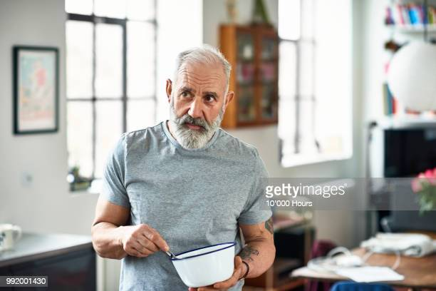 portrait of senior man holding bowl and preparing food - wegkijken stockfoto's en -beelden