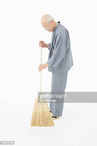Portrait of senior man holding broom, side view, studio shot