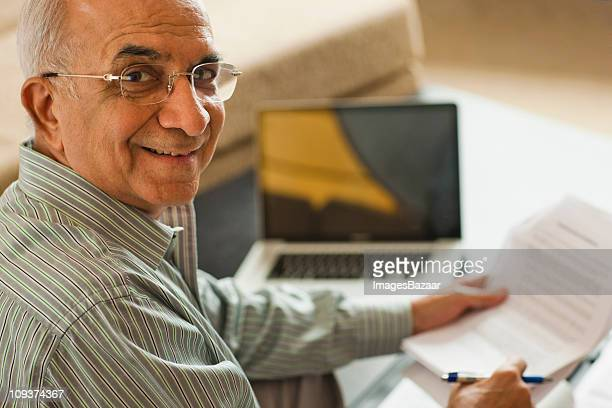 Portrait of senior man holding document near laptop on coffee table