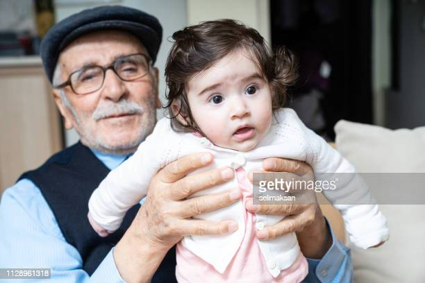 Portrait Of Senior Man Holding Great Granddaughter