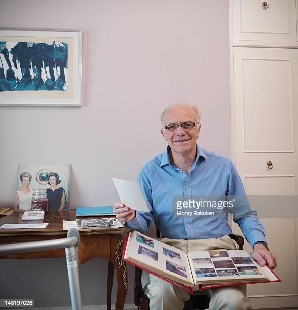 Portrait of senior man holding photograph album
