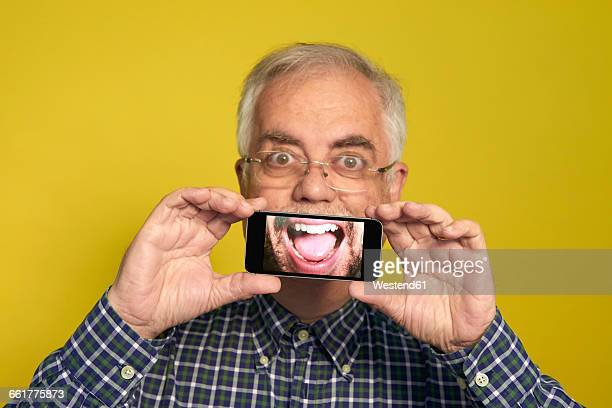 Portrait of senior man holding smartphone with photography of open mouth