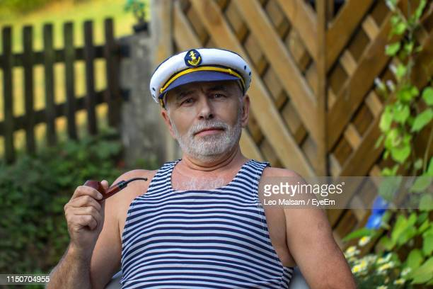 portrait of senior man holding smoking pipe - sailor hat stock pictures, royalty-free photos & images