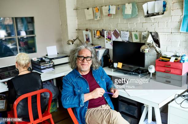portrait of senior man in creative home office - creative director stock pictures, royalty-free photos & images