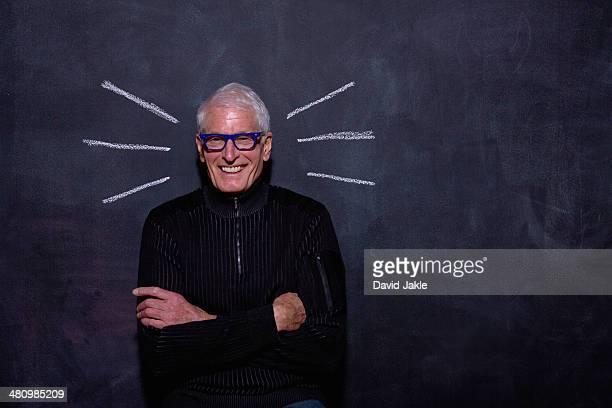 Portrait of senior man in front of chalked lines on blackboard