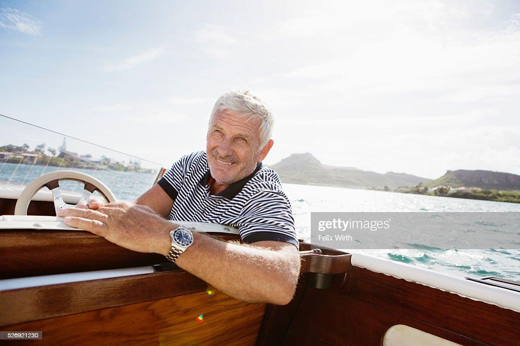 Portrait of senior man in motorboat : Stock Photo