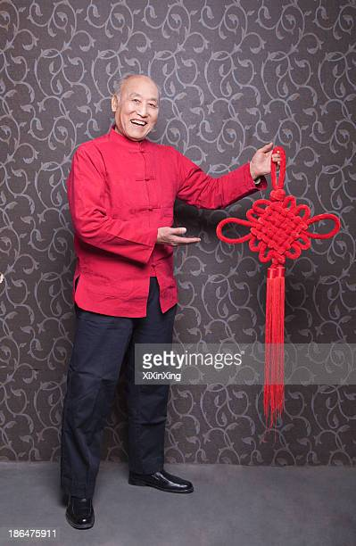 portrait of senior man in traditional chinese clothing holding tied knot - chinese knotting stock pictures, royalty-free photos & images