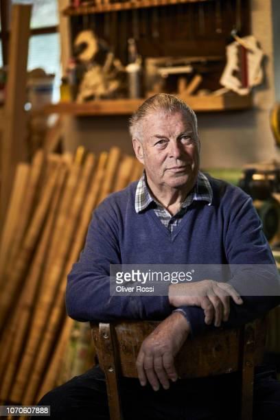 Portrait of senior man in workshop with alpenhorn instrument parts in background