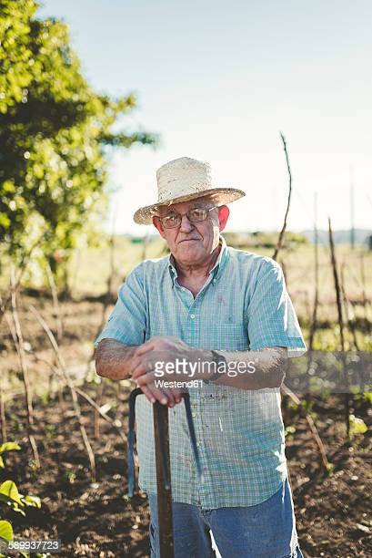 Portrait of senior man leaning on a hoe