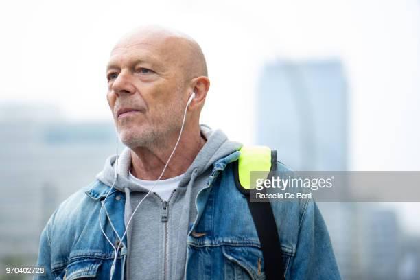 Porträt von senior woman Kopfhörer auf der Straße hören