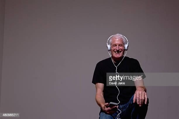 Portrait of senior man listening to MP3 player on headphones