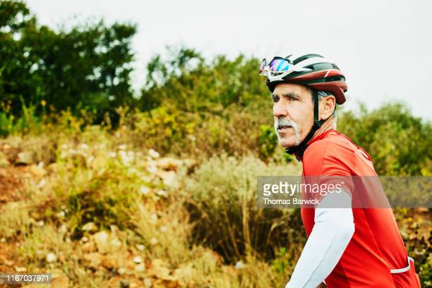portrait of senior man looking at trail before early morning mountain bike ride - disruptaging stock pictures, royalty-free photos & images