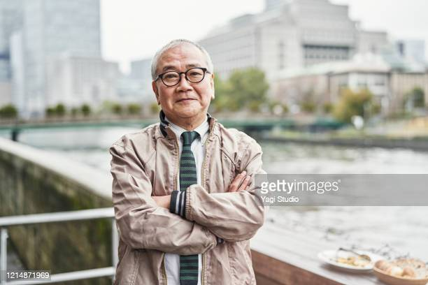 portrait of senior man on cafe terrace - japanese old man stock pictures, royalty-free photos & images