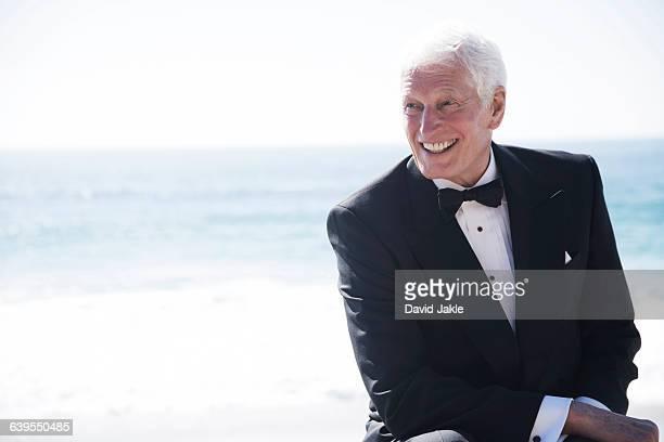 Portrait of senior man outdoors, wearing dinner jacket, smiling