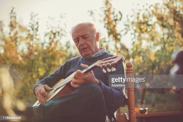 portrait of senior man playing guitar sitting - stringed instrument stock pictures, royalty-free photos & images