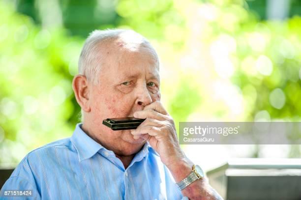 Portrait Of Senior Man Playing Harmonica