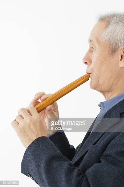 portrait of senior man playing japanese bamboo flute, side view, close-up, studio shot - bamboo flute foto e immagini stock