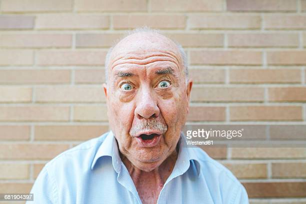 portrait of senior man pulling funny faces - faszination stock-fotos und bilder