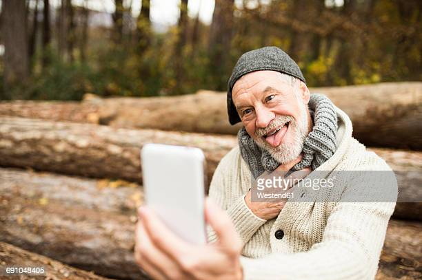 portrait of senior man pulling funny faces while taking selfie - white hair stock photos and pictures