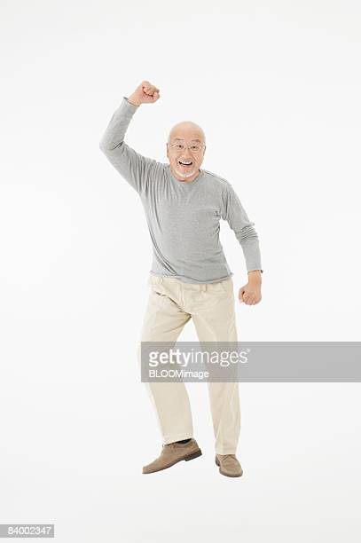 Portrait of senior man raising fist, studio shot