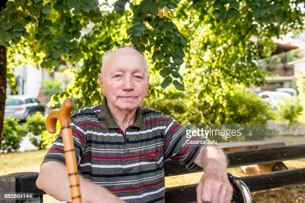 Portrait Of Senior Man Relaxing In The Backyard Of The Nursing Home