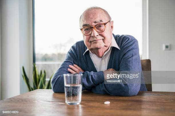 portrait of senior man sitting at table with pill and glass of water - medicijnen innemen stockfoto's en -beelden