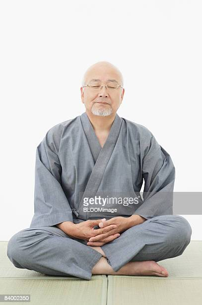 Portrait of senior man sitting cross-legged, with eyes closed, hands clasped, studio shot