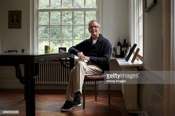Portrait of senior man sitting in cottage