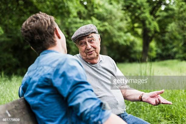 portrait of senior man sitting on a bench talking to his grandson - sitzbank stock-fotos und bilder