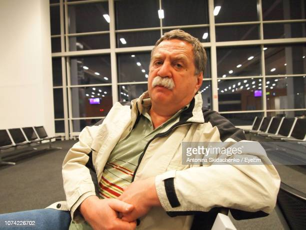 Portrait Of Senior Man Sitting On Chair At Airport Departure Area