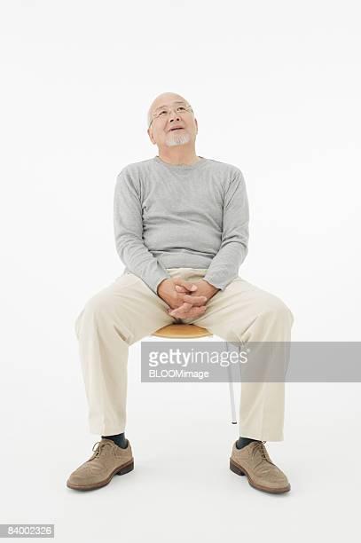 Portrait of senior man sitting on chair, clasping hands, studio shot