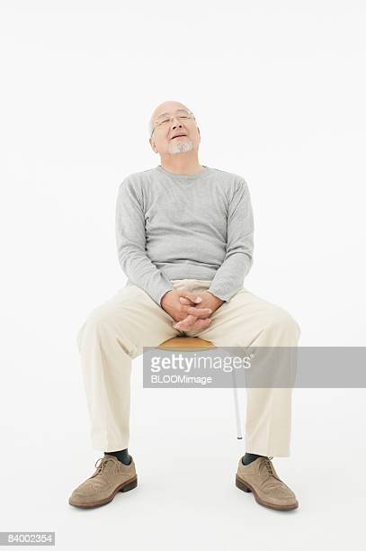 Portrait of senior man sitting on chair, eyes closed, clasping hands, studio shot