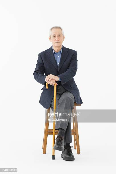Portrait of senior man sitting on chair with legs crossed, holding cane, studio shot