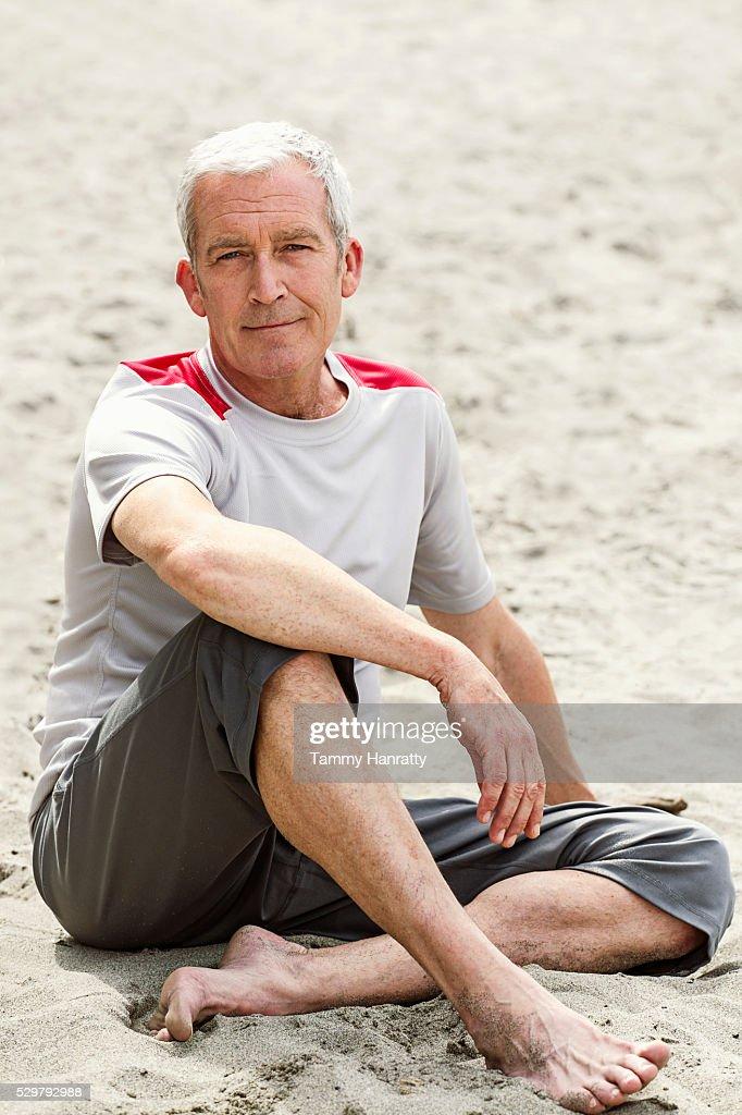 Portrait of senior man sitting on sand looking at camera : Stock Photo