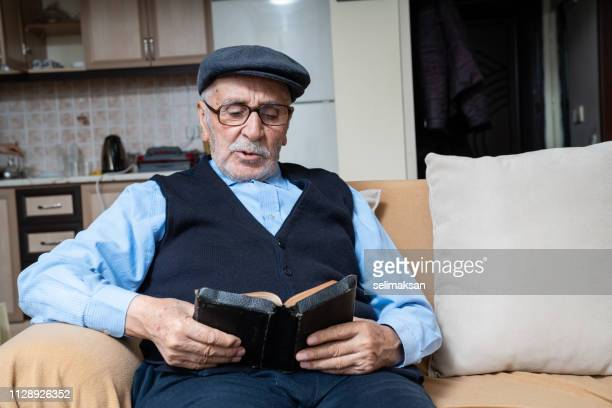 Portrait Of Senior Man Sitting On Sofa And Reading Book