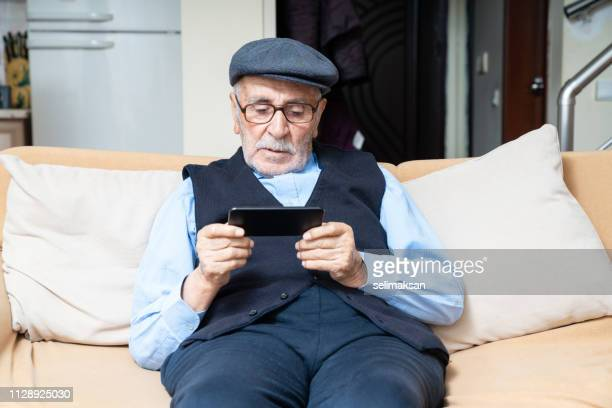 Portrait Of Senior Man Sitting On Sofa In Living Room And Using Mobile Phone