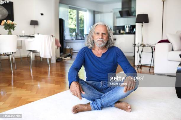 portrait of senior man sitting on the floor at home - manches longues photos et images de collection
