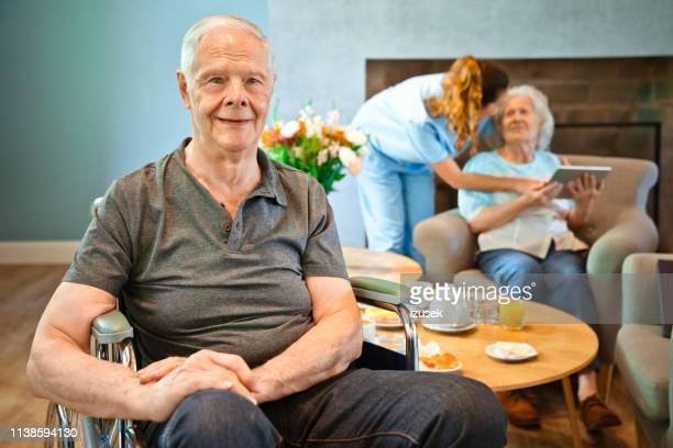 ritratto di uomo anziano seduto su sedia a rotelle - izusek foto e immagini stock