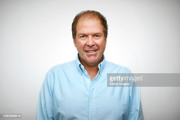 portrait of senior man smiling against white - receding hairline stock pictures, royalty-free photos & images