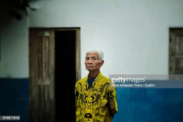 portrait of senior man standing against wall - java indonesia fotografías e imágenes de stock