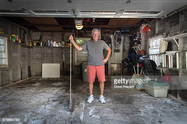 portrait of senior man standing in garage holding broom - neat stock pictures, royalty-free photos & images