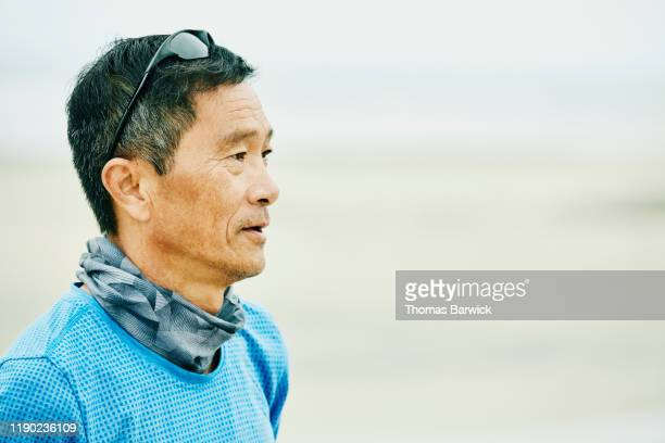 portrait of senior man standing on beach during early morning workout - athlete stock pictures, royalty-free photos & images