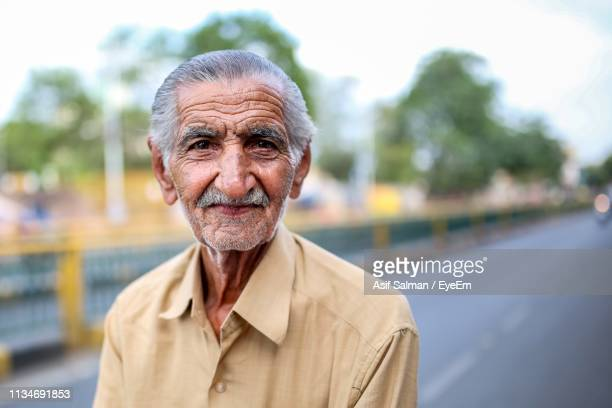 portrait of senior man standing on road against sky - indian subcontinent ethnicity stock pictures, royalty-free photos & images