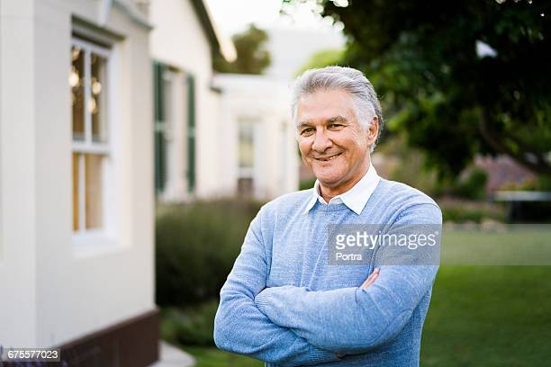 portrait of senior man standing outside house - one man only stock pictures, royalty-free photos & images